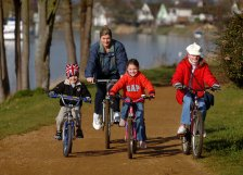 Family cycling along the River Thames