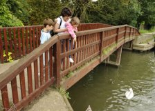 A family playing pooh sticks in Goring